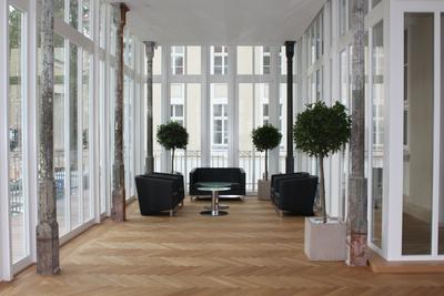 Wintergarten: Im Wintergarten zeigt sich die Symbiose aus alten, erhaltenen Baumaterialien und neuen Oberflächen.